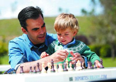 Enseñando a un niño a jugar al ajedrez en el parque.