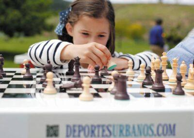 Niña jugando en una mesa de ajedrez al aire libre.