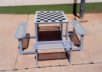 Mesa de ajedrez con bancos de acero en espacio público.