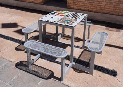 Mesa con juegos de mesa con bancos de acero en espacio público.