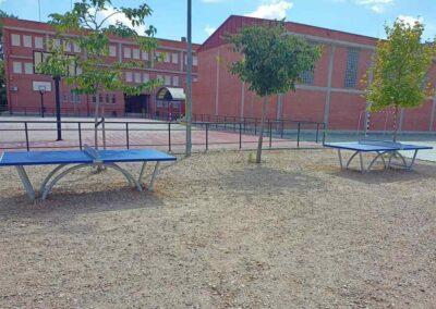 2 mesas de ping pong Sport en un patio de colegio.