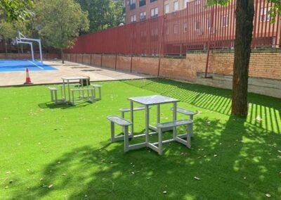 Mesas de juegos y canastas de basket en un patio de colegio.